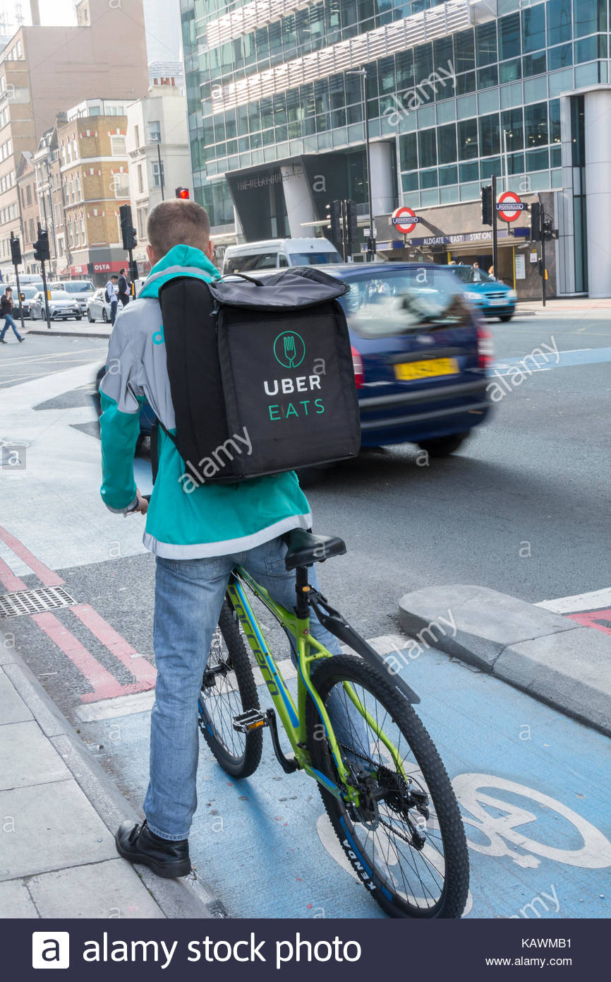 An Uber Eats delivery cyclist outside Uber Headquarters in Aldgate Tower, Whitechapel, London, UK - Stock Image