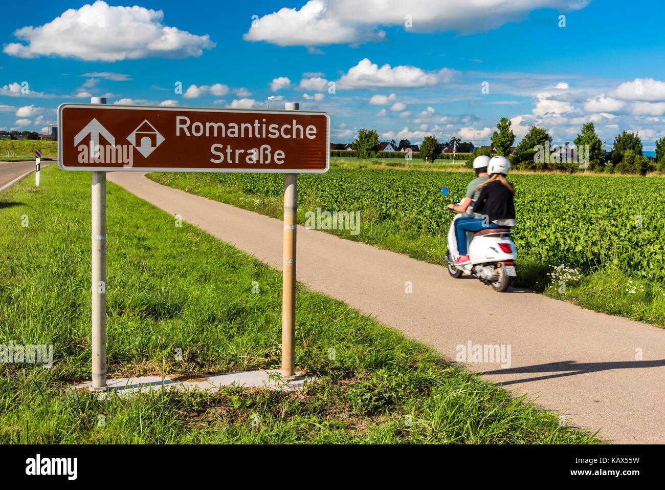 Car passing near a Romantische Strasse (Romantic Road) road sign, Nordlingen, Bavaria, Germany - Stock Image