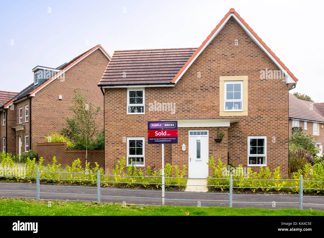 Purple Bricks sold estate agent sign in front of new build house UK - Stock Image