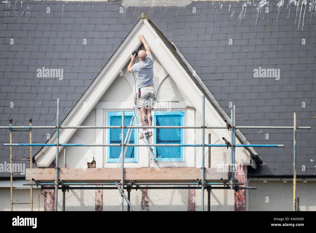 Man precariously standing on step ladder on scaffolding while repairing woodwork around house window. UK - Stock Image