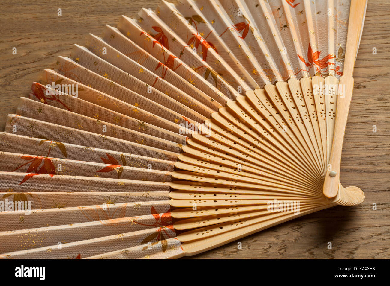 Traditional Japanese hand fan decorated with autumn maple leaves - Stock Image