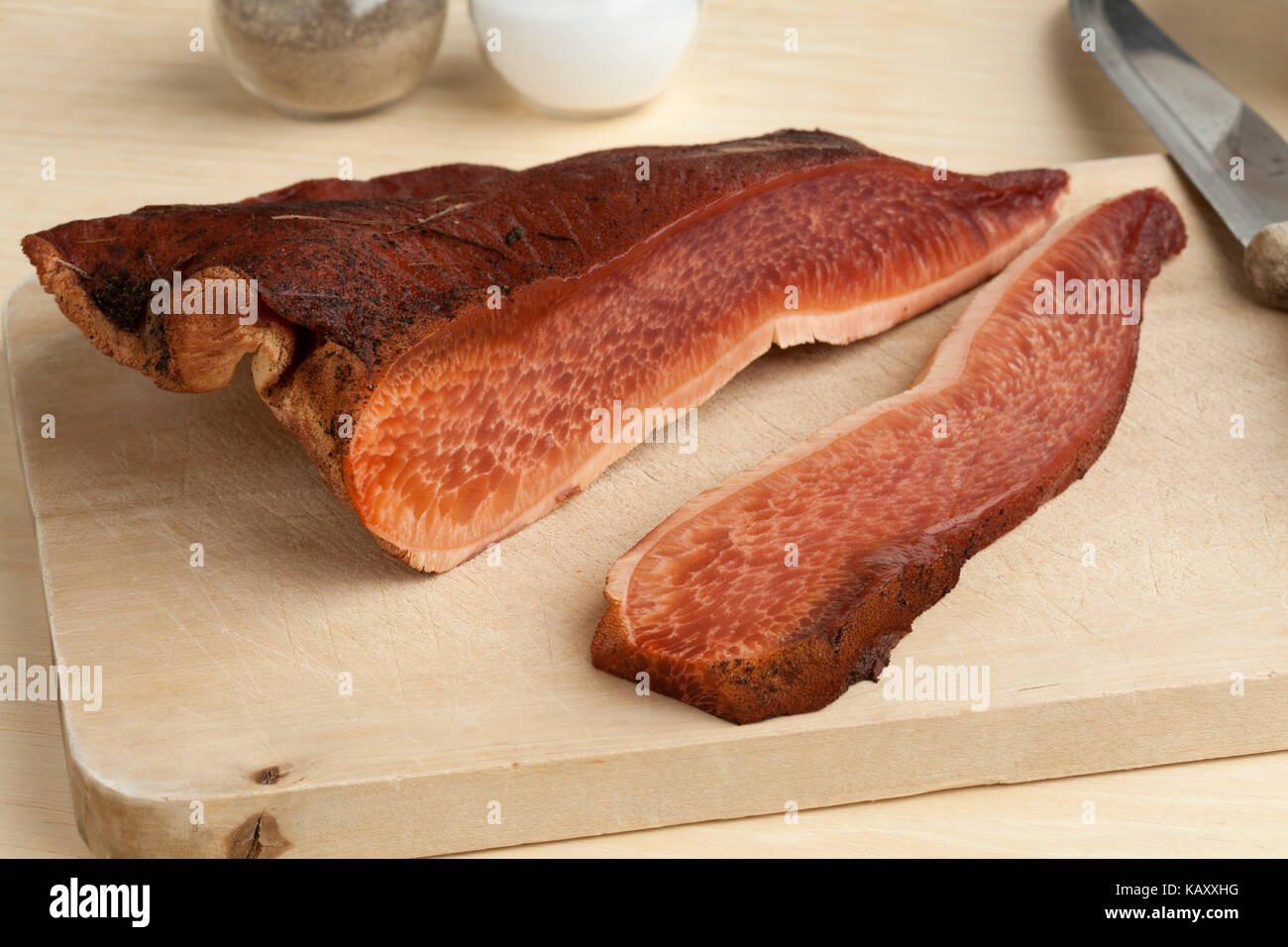 Fresh slice of a beefsteak fungus on a cutting board - Stock Image