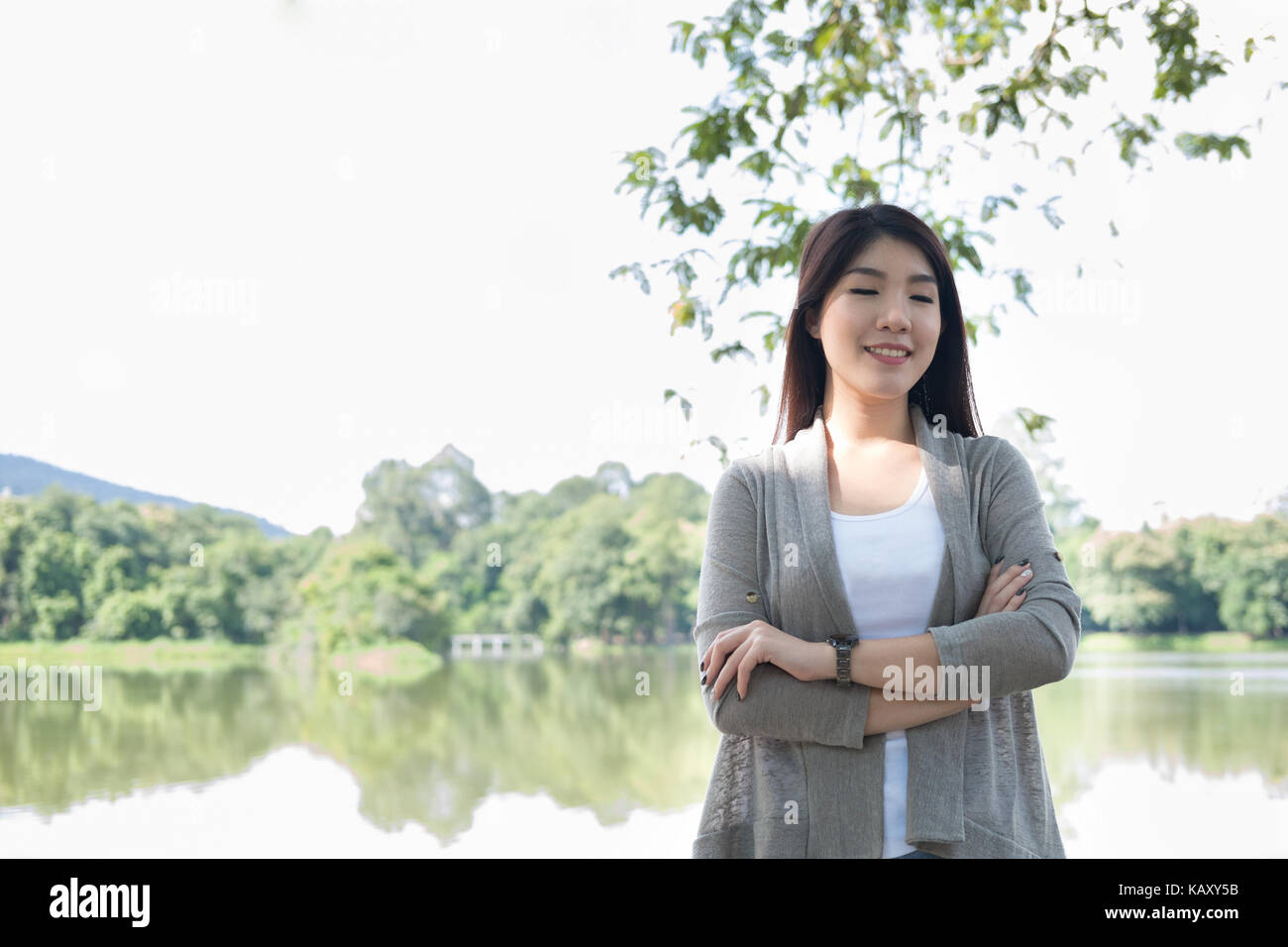 pretty asian woman portrait. young female adult with natural make-up relax in park. attractive teenager smile with - Stock Image