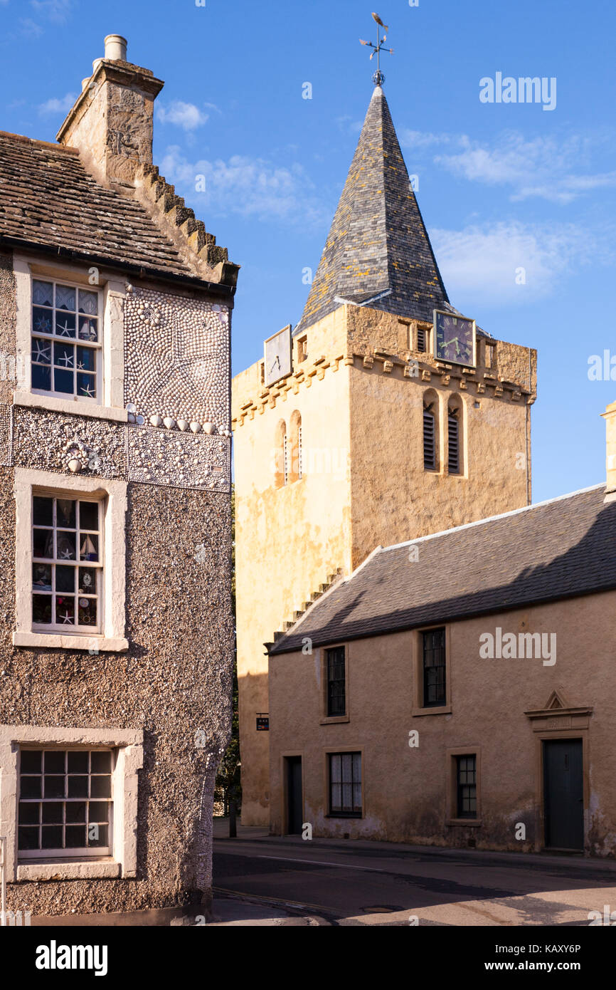 Evening light on the church and Buckie House (1692) decorated with shells in the fishing village of Anstruther, - Stock Image