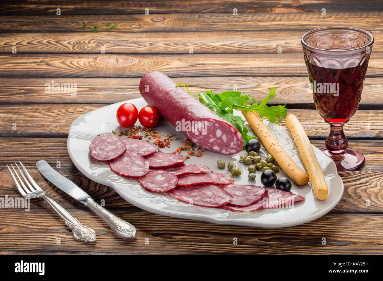 Sausage with red wine, olives, capers, tomates and harbs over wooden background - Stock Image