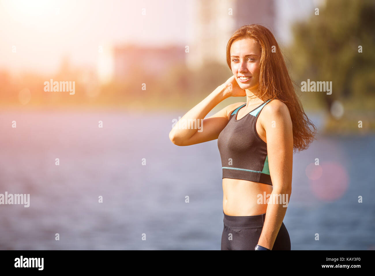 Portrait of young sporty woman resting after jogging in park near lake. Portrait of athletic girl in black top after - Stock Image