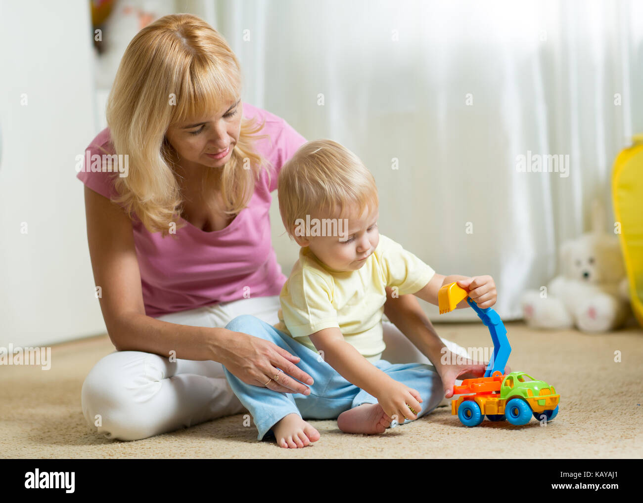 Childtoddler playing car toy in his room or nursery - Stock Image