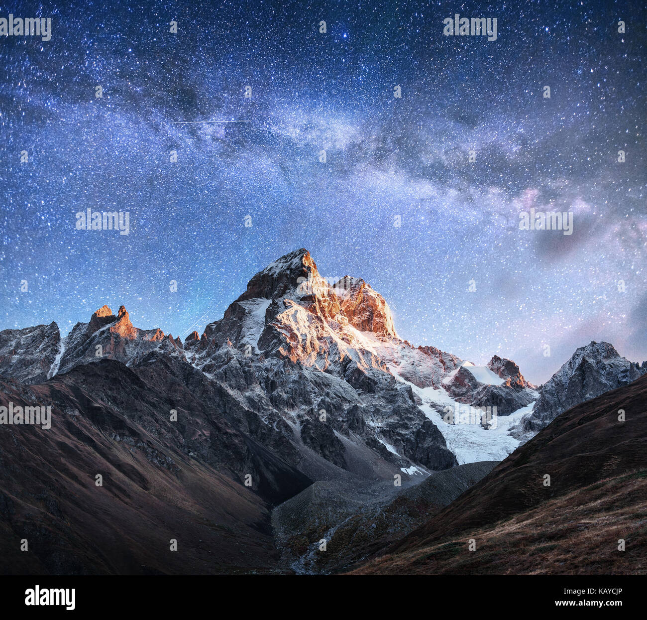 Fantastic starry sky. Autumn landscape and snow-capped peaks. Main Caucasian Ridge. Mountain View from Mount Ushba - Stock Image
