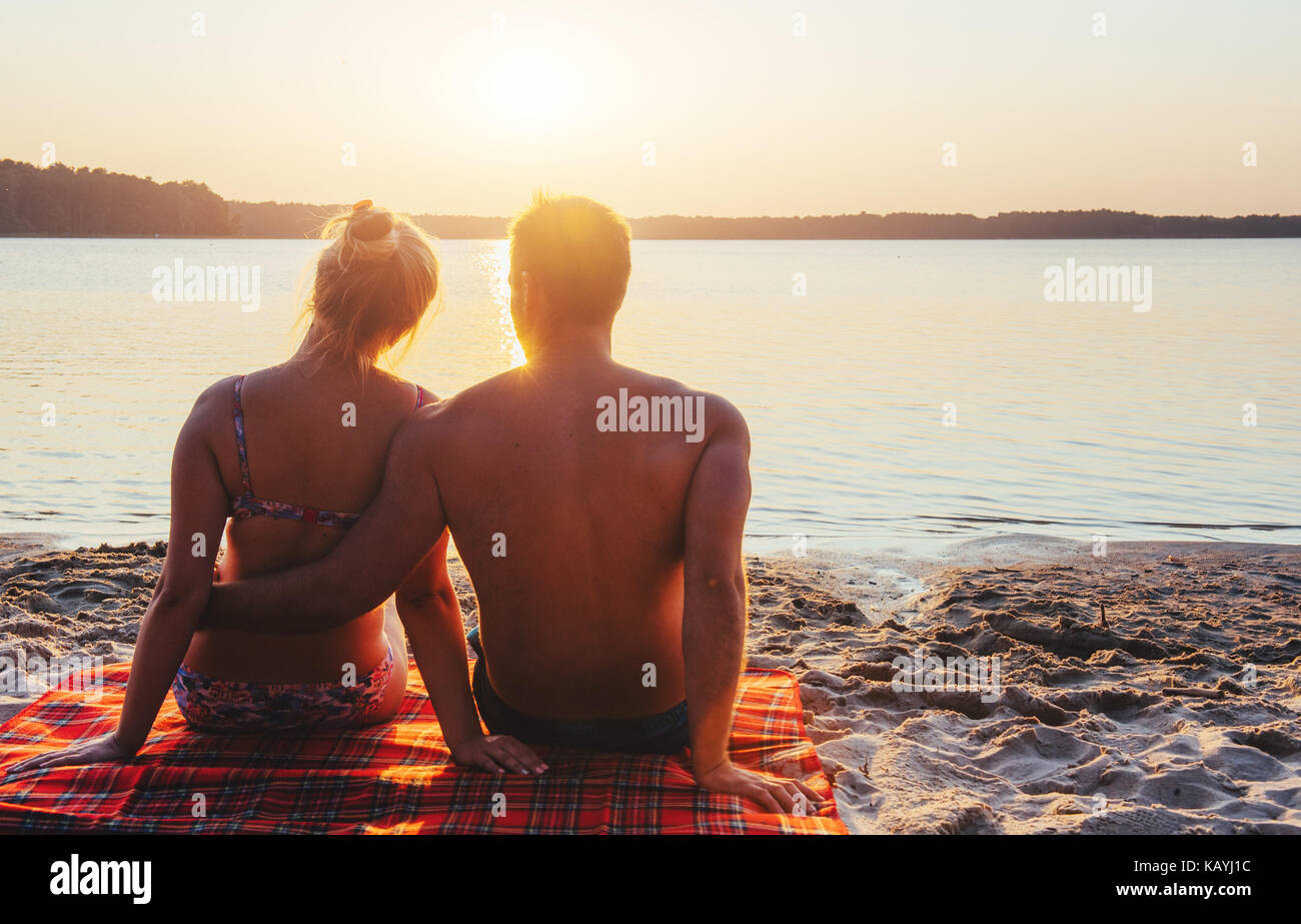 Romantic couple on the beach at colorful sunset on background Stock Photo