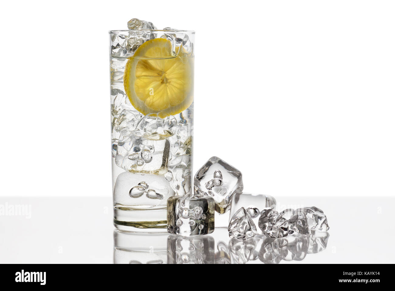 glass full of fresh water with lemon slice and ice cubes on background - Stock Image