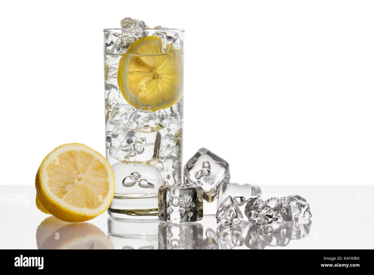 glass full of fresh water with lemon and ice cubes on background - Stock Image