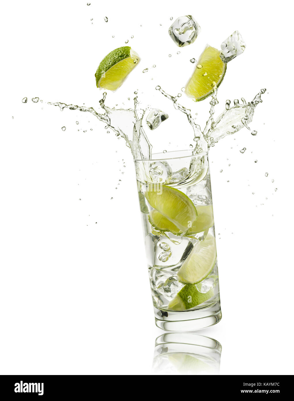glass full of water with lime slices and ice cubes falling and splashing water, on white background - Stock Image