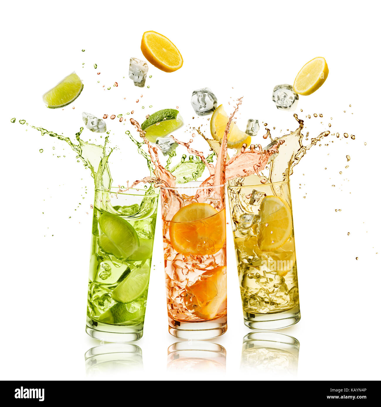 citrus fruits soft drink with fruit slices and ice cubes falling and splashing, on white background - Stock Image