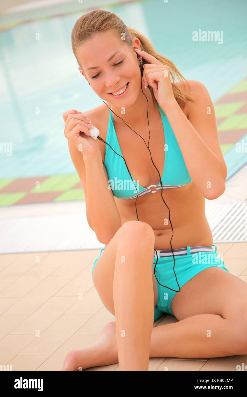 young blond woman hears music with MP3-player in the swimming-pool, - Stock Image