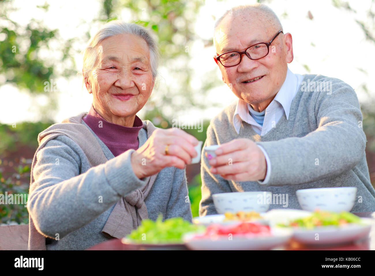 happy and healthy Chinese senior couple together eating in the garden - Stock Image