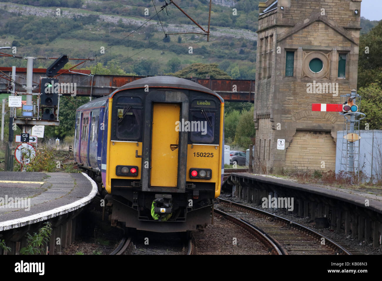 Class 150 Sprinter diesel multiple unit train in Northern livery leaving Carnforth railway station with a passenger - Stock Image