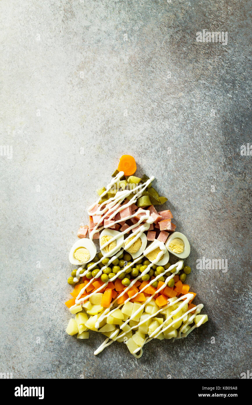 Christmas tree made from salad olivier on a gray slate, stone or metal background. Beautiful Christmas and New Year - Stock Image