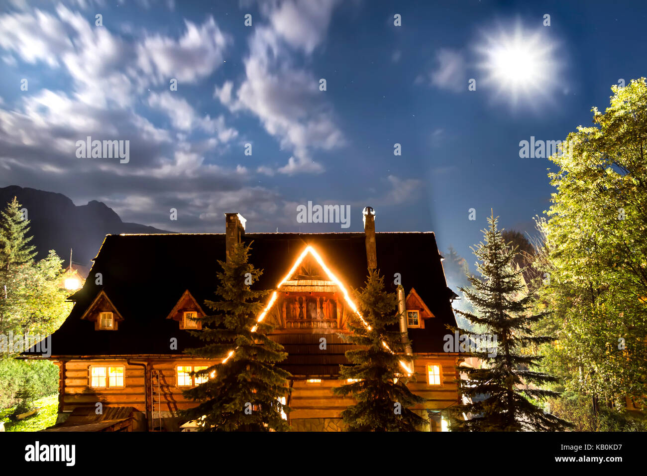 High mountain in Poland. National Park - Tatras. Ecological reserve.  Old country house against sky .Shining moon. - Stock Image