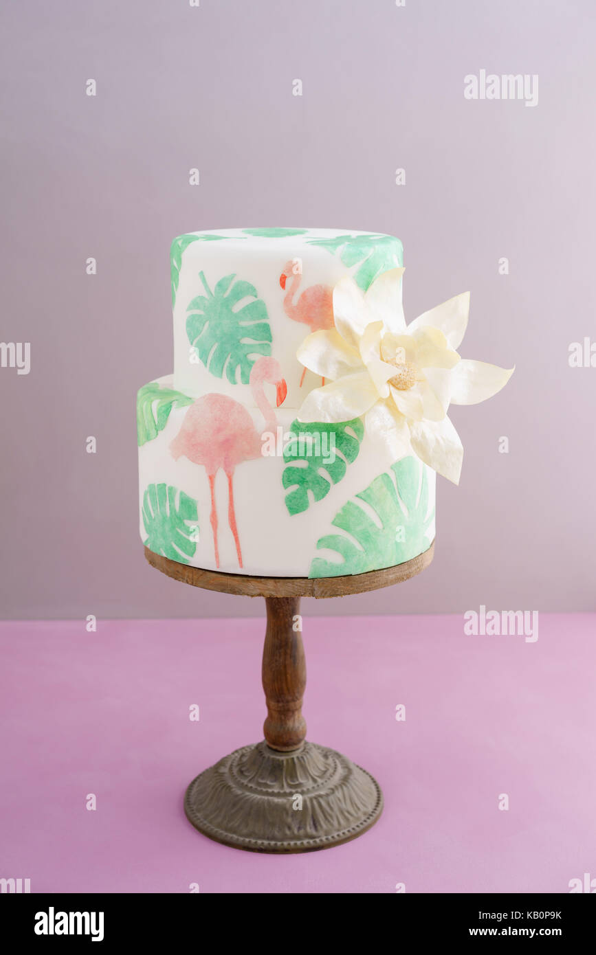 Two tiered tropical wedding cake with fondant, tropical wafer paper leaves and flamingos with a big golden statement - Stock Image