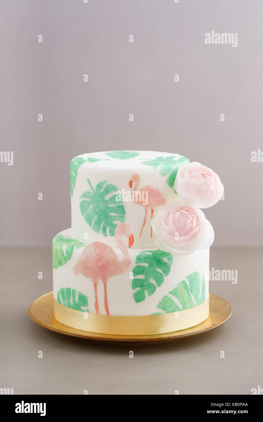 Two tiered tropical wedding cake with fondant, tropical wafer paper leaves and flamingos with ranunculus flowers - Stock Image