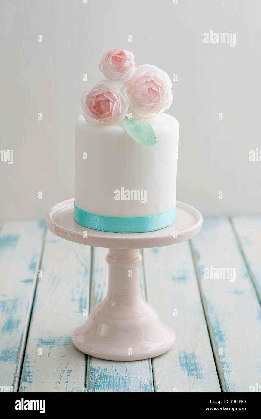 Mini white fondant covered wedding cake with wafer paper ranunculus flowers on pink cake stand with turquoise ribbon - Stock Image
