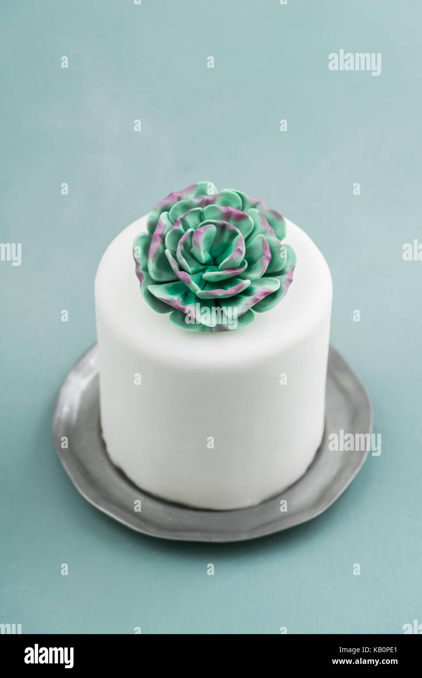 White mini wedding cake covered with fondant with gum paste succulent on a pewter plate - Stock Image