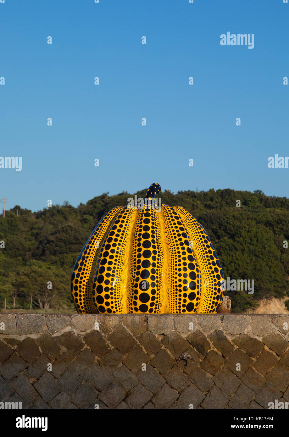 Yellow pumpkin by yayoi kusama on pier at sea, Seto Inland Sea, Naoshima, Japan - Stock Image