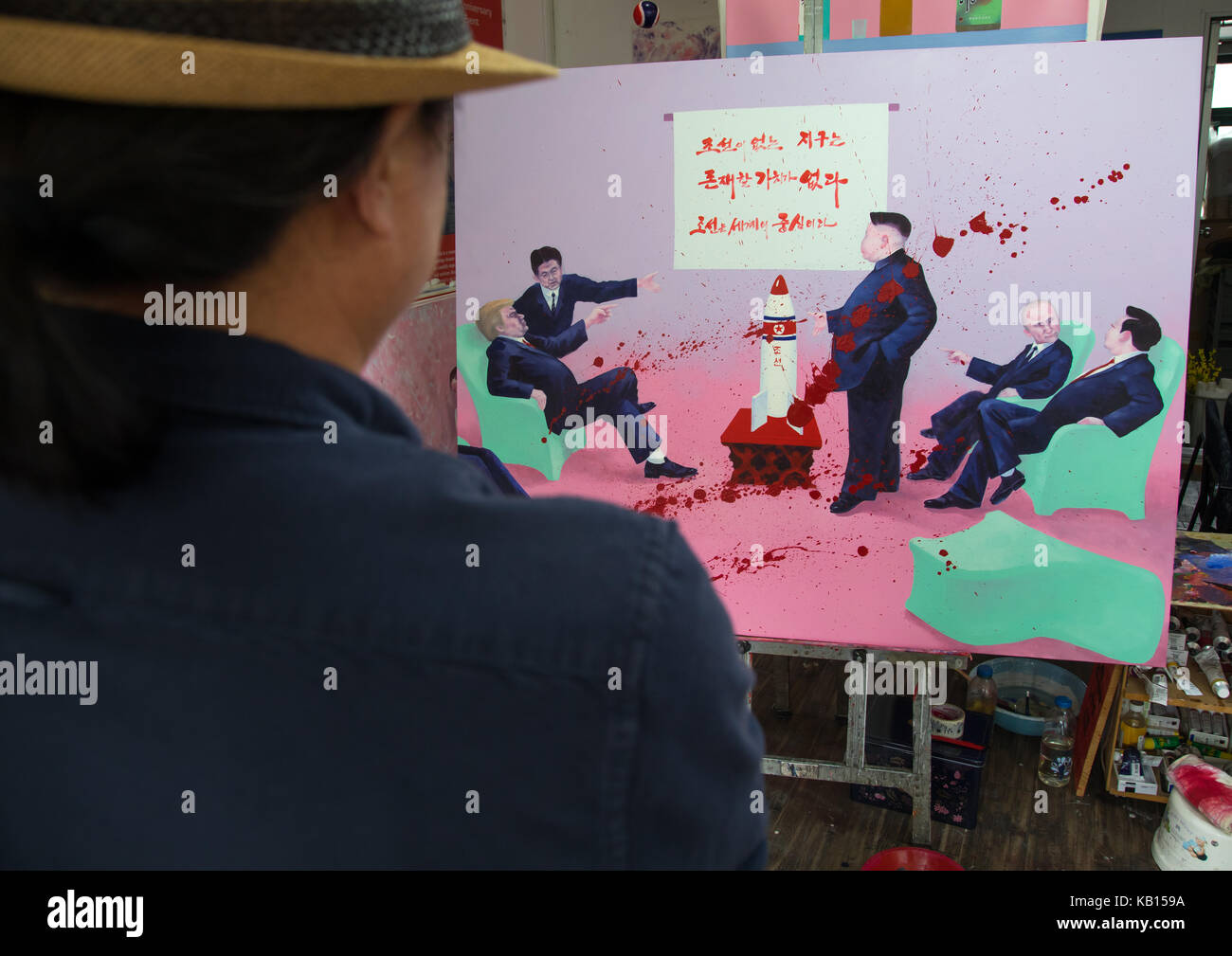 North korean artist sun mu in frot of a painting with donald trump and kim jong un, National Capital Area, Seoul, - Stock Image