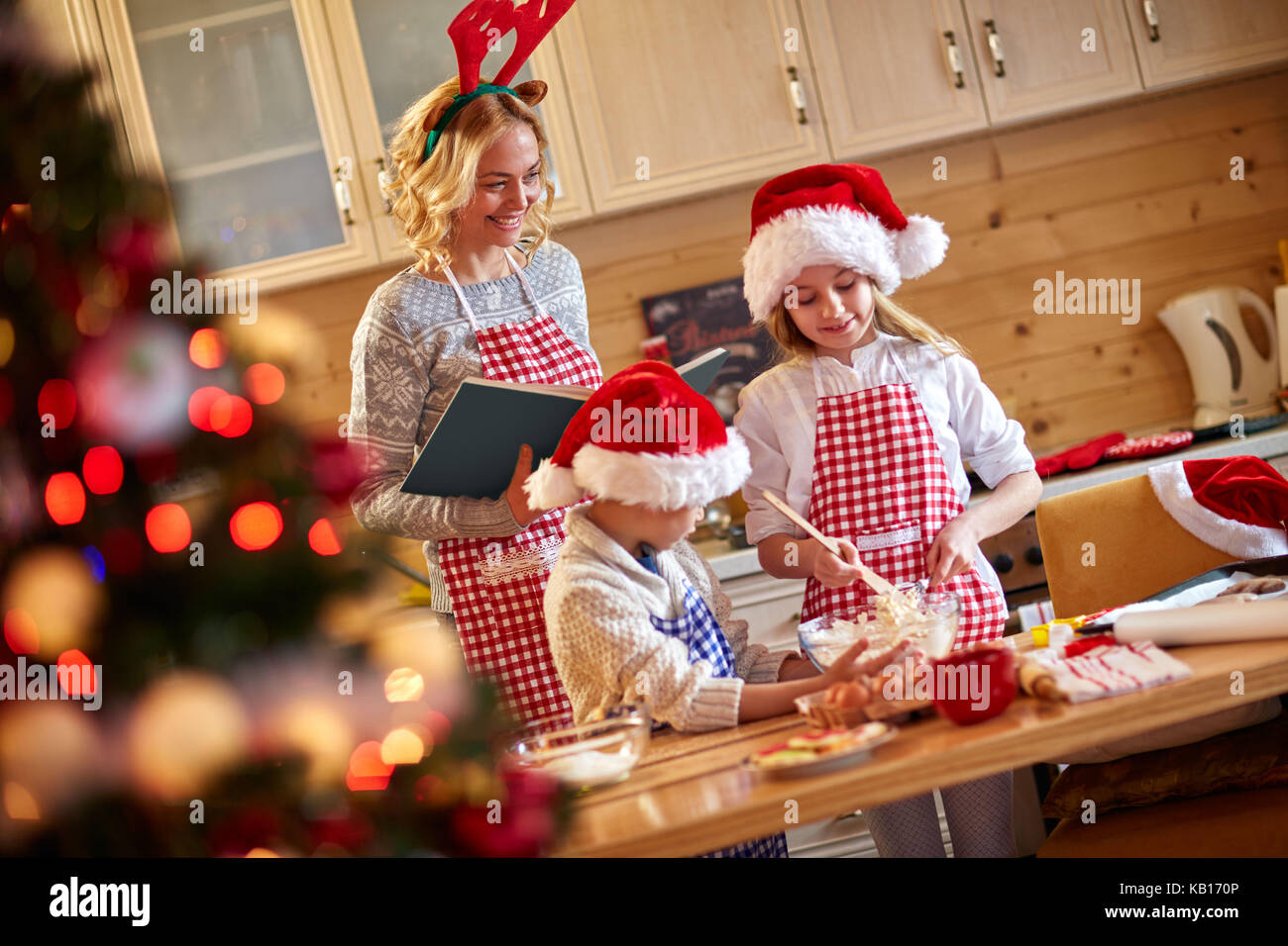 mother helping children at making christmas cookies family time stock image - Making Christmas Cookies