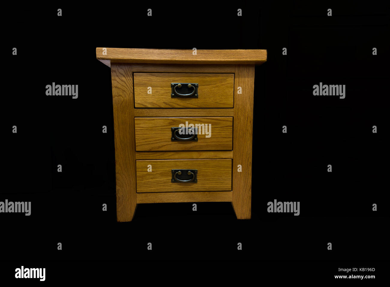 A set of antique handled oak drawers isolated on a black back ground with smiley handles - Stock Image