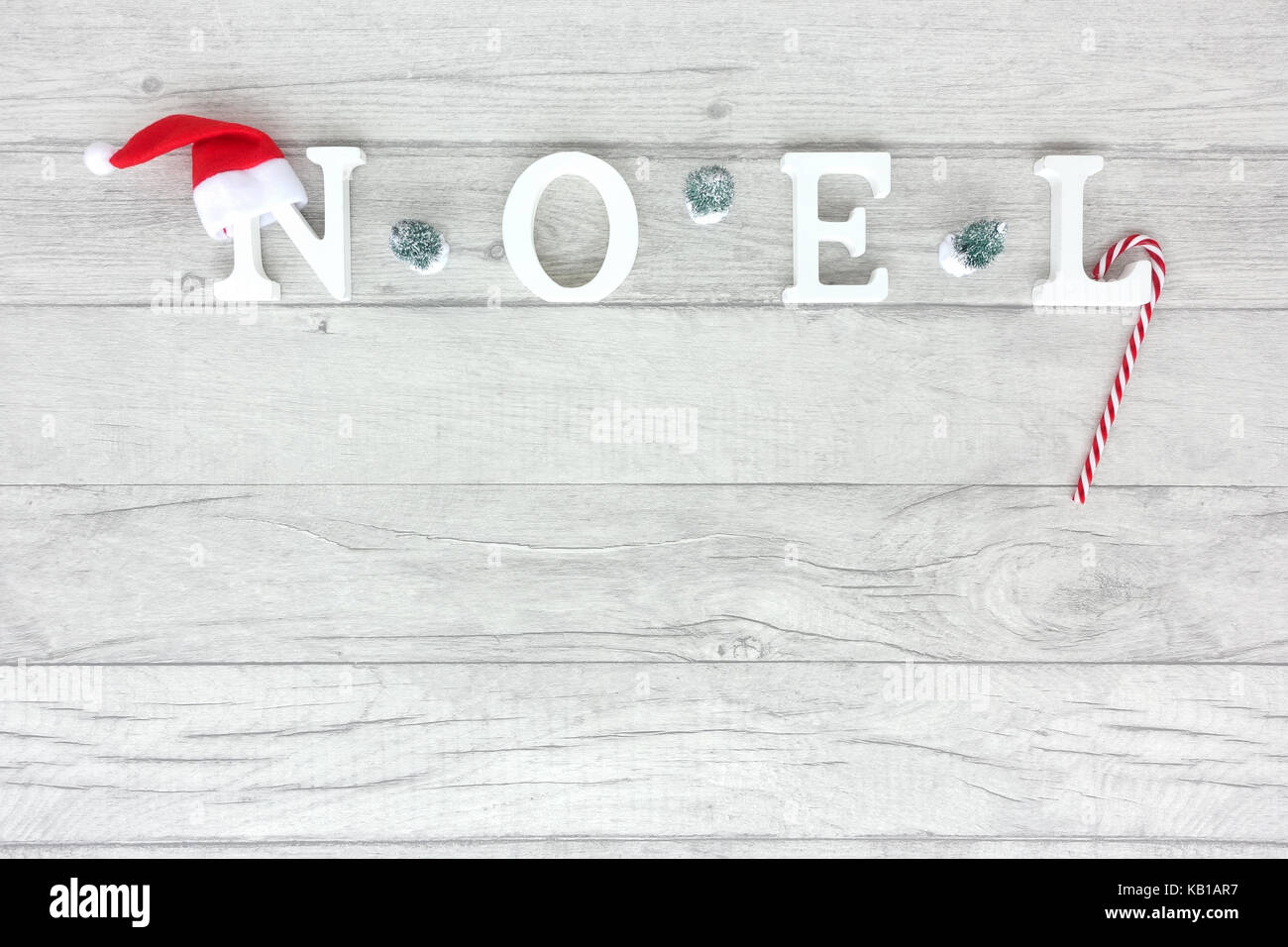Christmas background with the words noel formed out of white wooden capital letters on grey wood background. - Stock Image