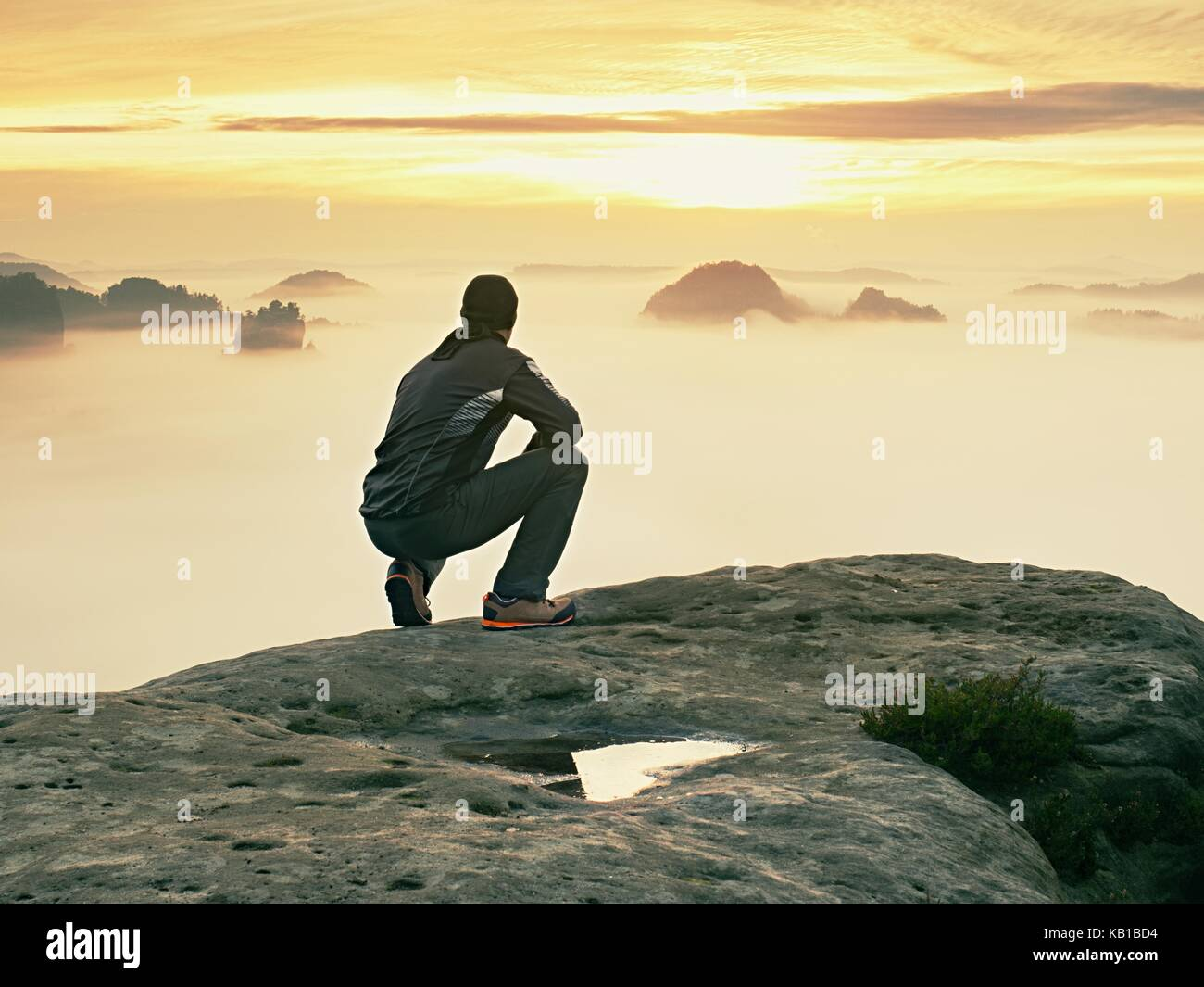 Tourist sit on peak of sandstone rock and watching into colorful mist and fog in  morning valley. Sad man. Man sit. Stock Photo