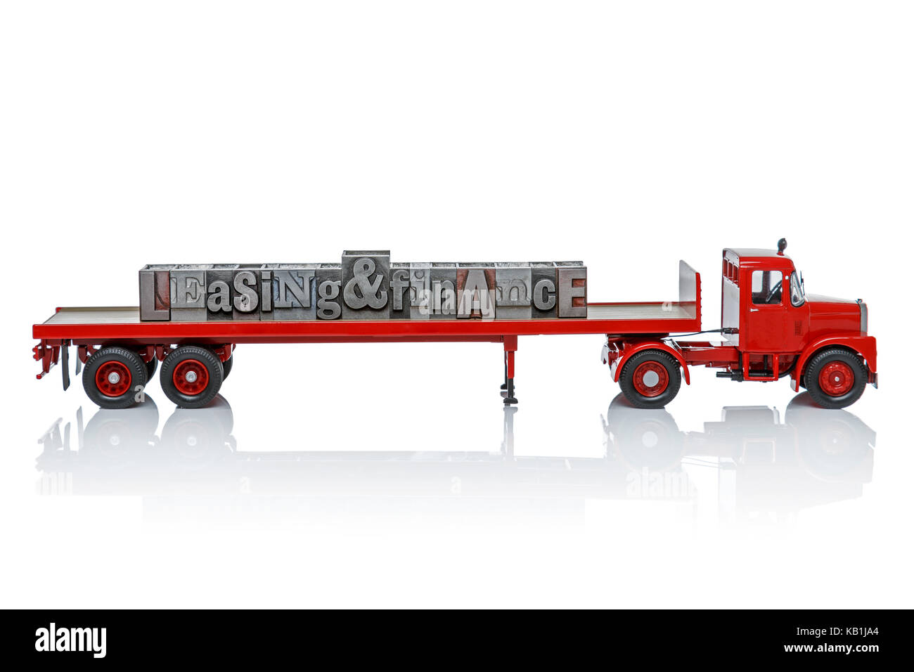 A toy truck with the words Leasing and Finance on the back made for old letterpress blocks. Isolated on a white - Stock Image