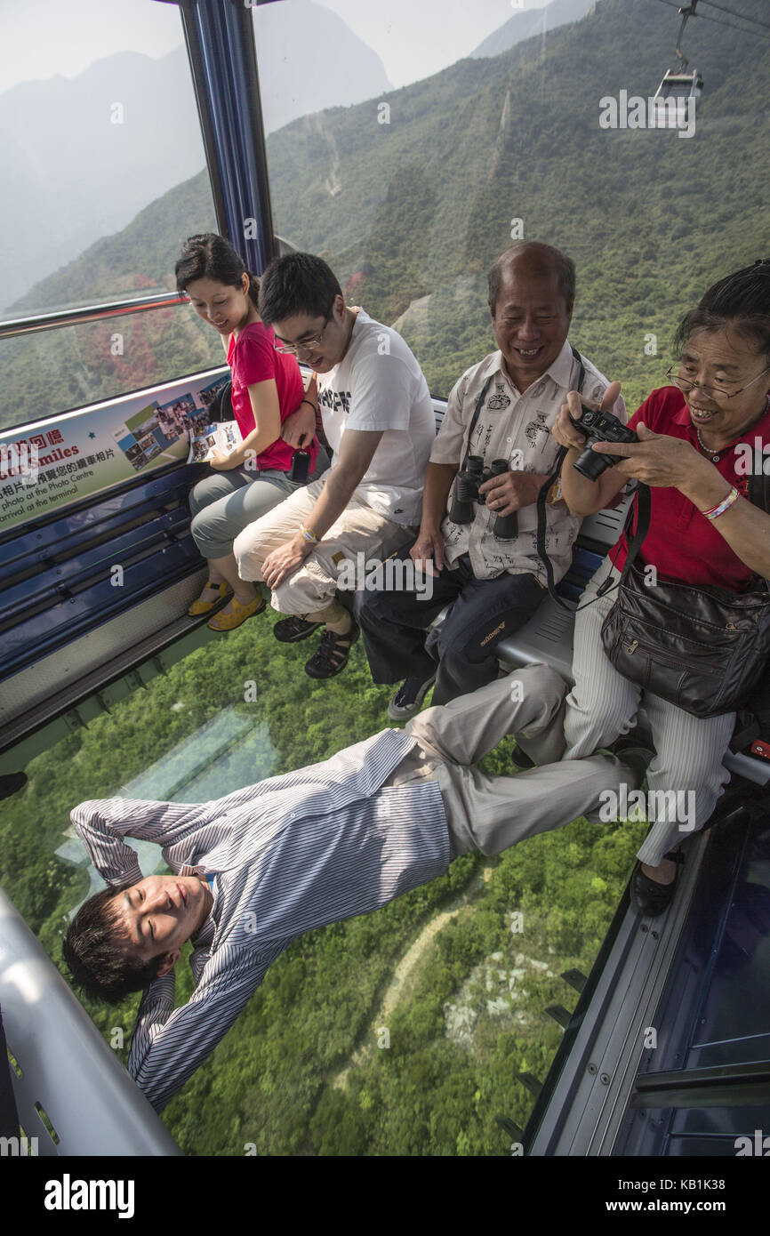 Tourists in a cable car, Lantau Iceland, Hong Kong, - Stock Image
