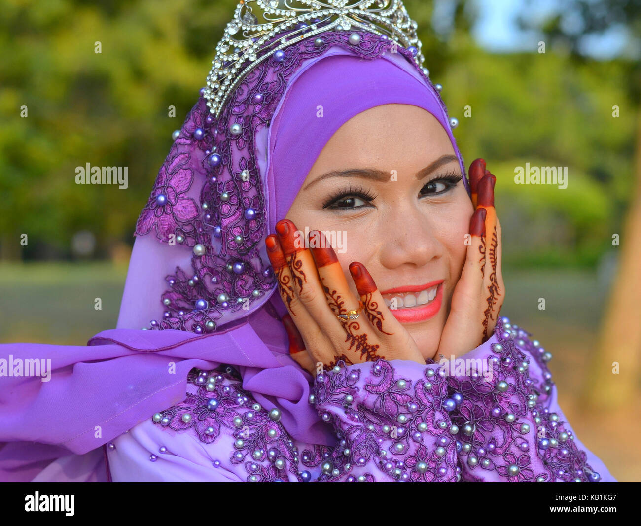 Beautiful traditional Muslim Malay bride with elaborate makeup and bridal henna on both her hands, wearing a blue - Stock Image