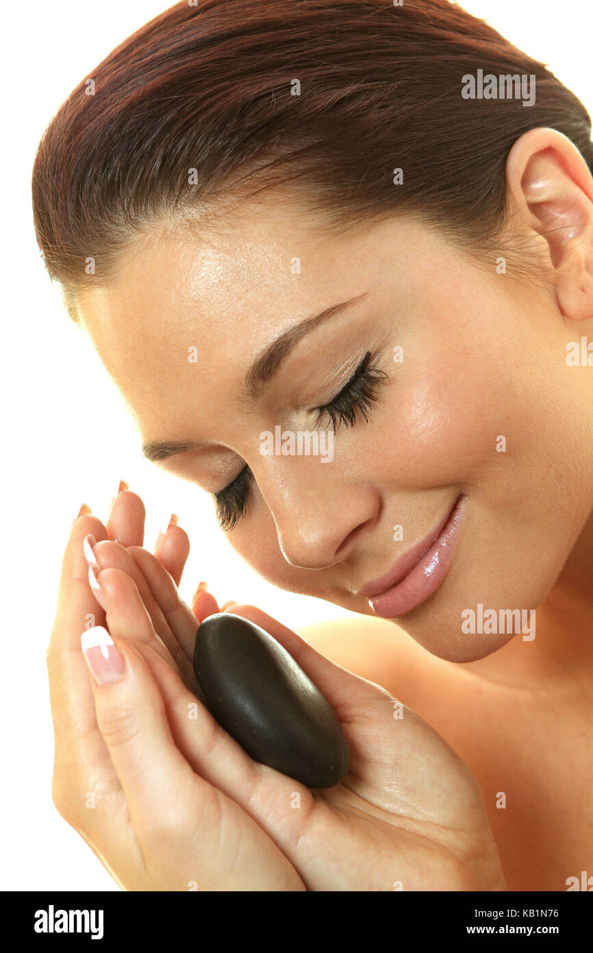 Young pretty woman massages her face with Hot Stone, - Stock Image