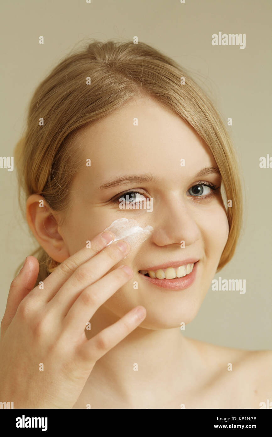 Young teenager girl while serving of face cream, - Stock Image