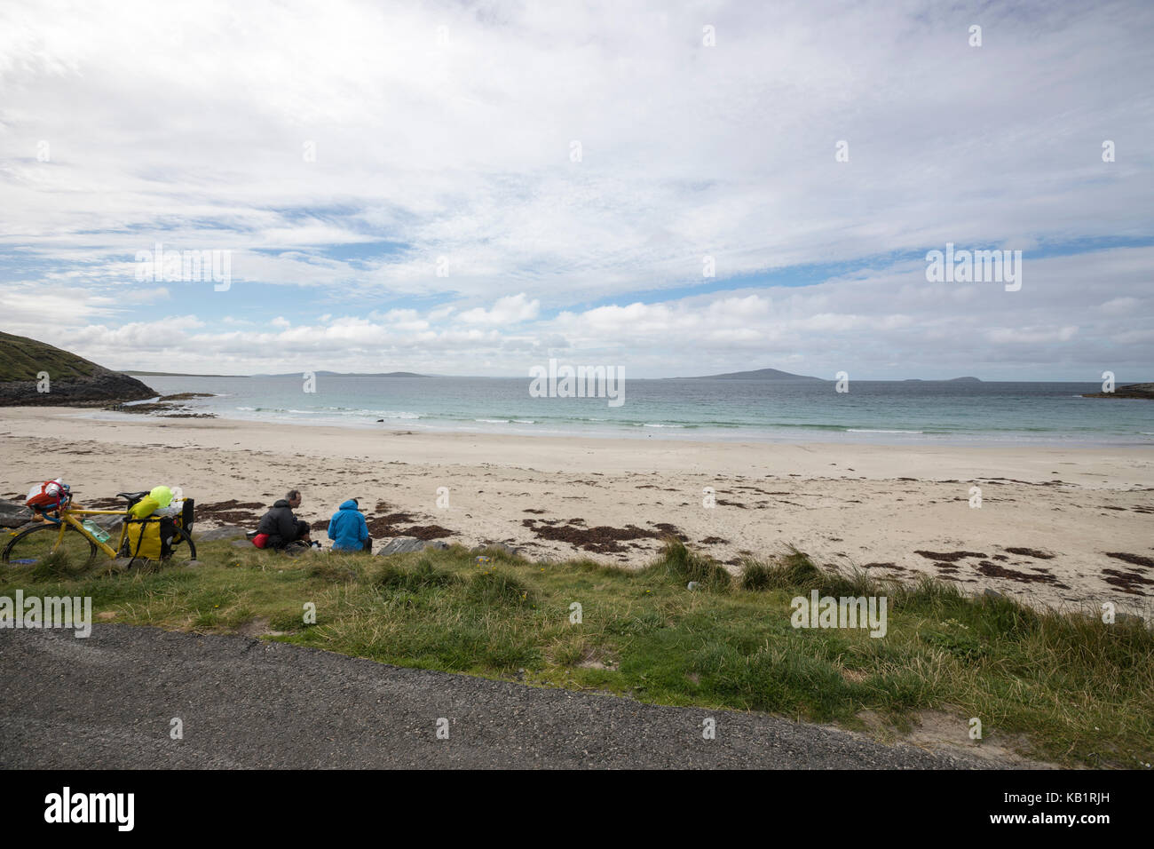 Two cyclist resting in front of a beach in Lewis and Harris island, Outer Hebrides, Scotland - Stock Image