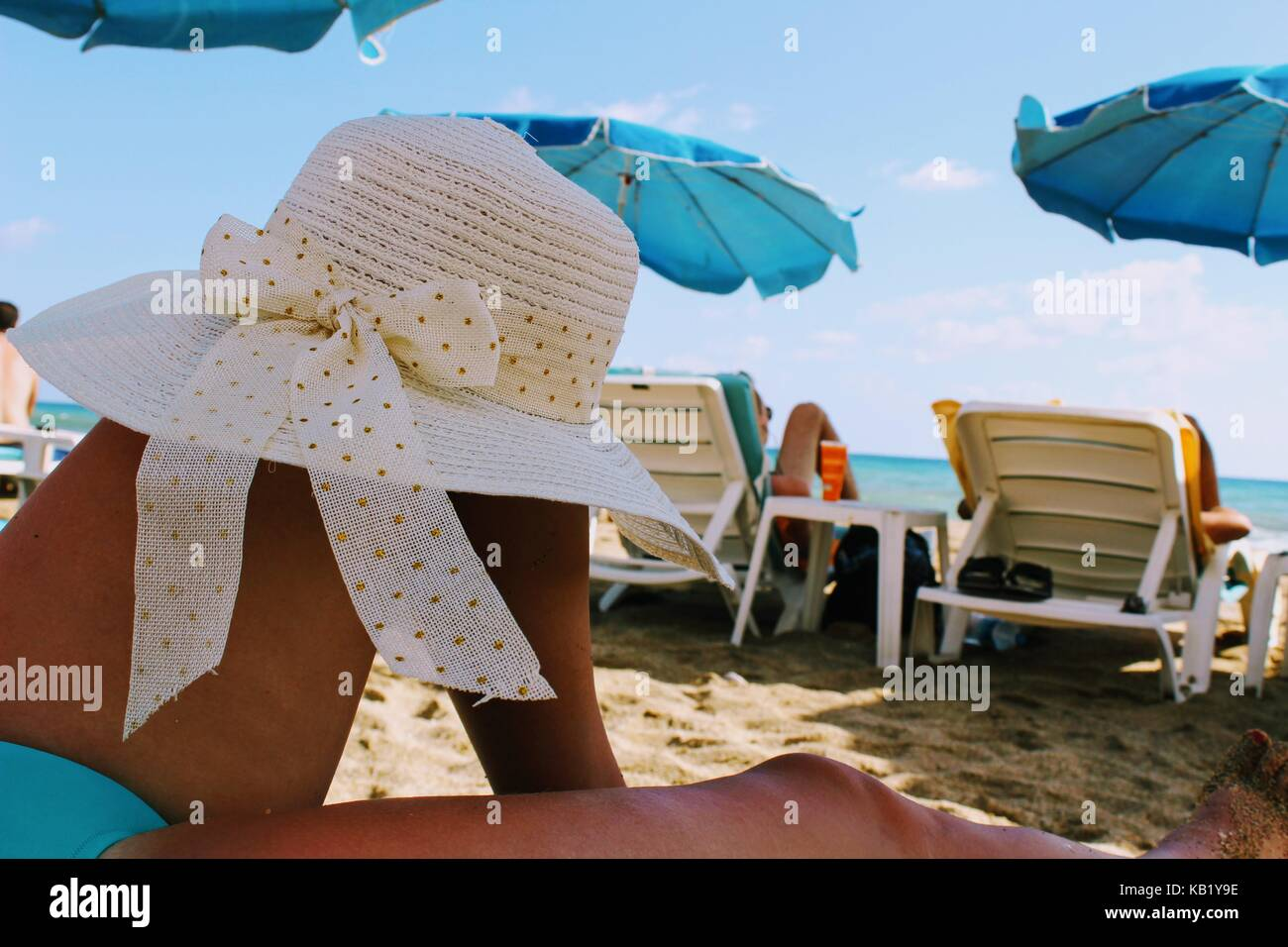 A white hat with wide brim is put on the bent knee of a woman lying on a deckchair on the beach. - Stock Image