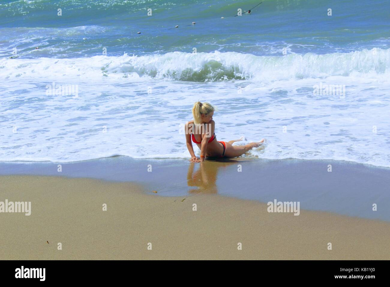 July, 2017 - A woman in a red swimsuit in the surf on the seashore at Cleopatra Beach (Alanya, Turkey). Stock Photo