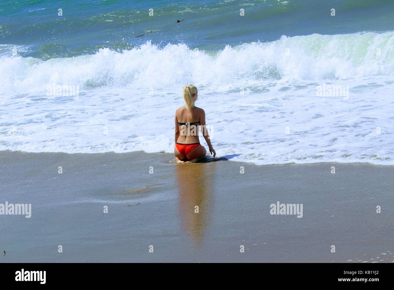 July, 2017 - A woman in a red swimsuit in the surf on the seashore at Cleopatra Beach (Alanya, Turkey). - Stock Image