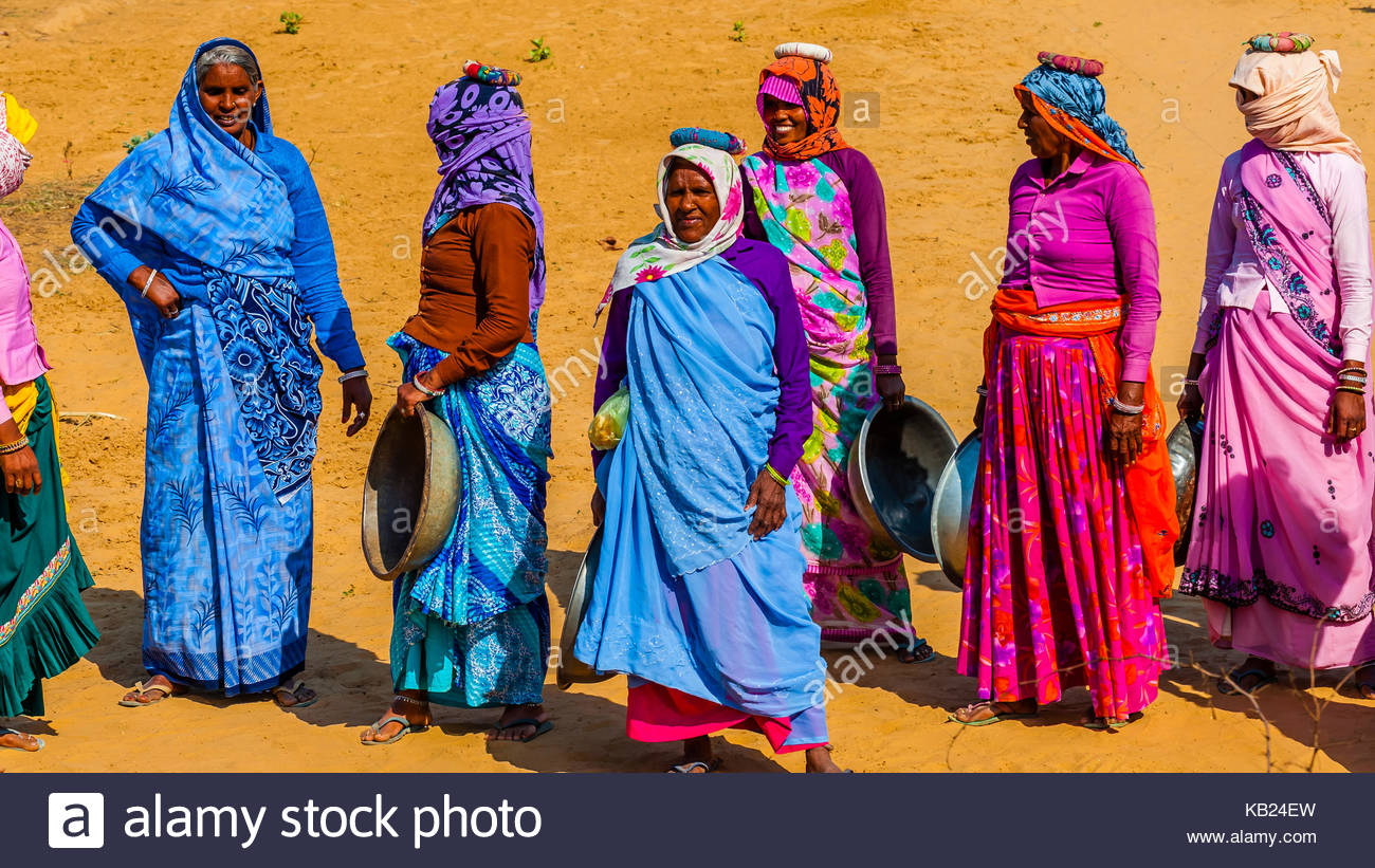 Rajasthani women in bright colors working (carrying dirt) at a construction project along the Jaipur-Agra Road, Stock Photo
