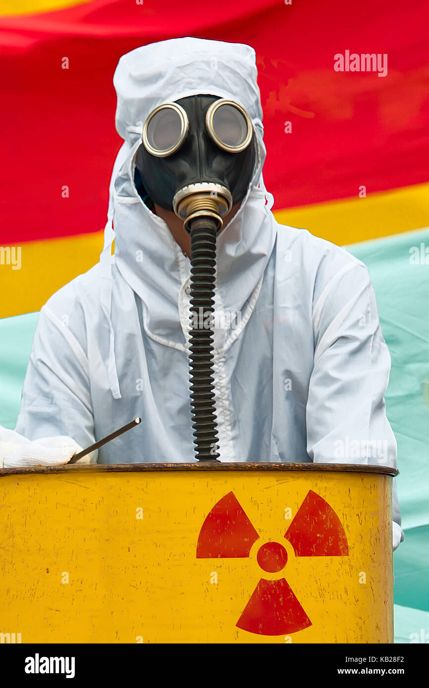 A man in bio-hazard suit and gas mask. A man in bio hazard suit and gas mask standing behind a rusty tank with nuclear - Stock Image