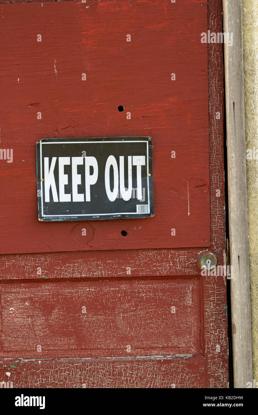 An old door with a keep out sign - Stock Image