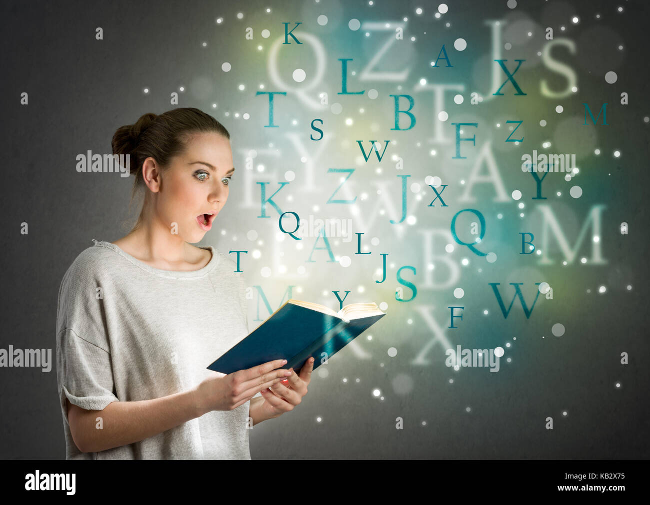 girl with astonishment looks in the book from which fly letters - Stock Image