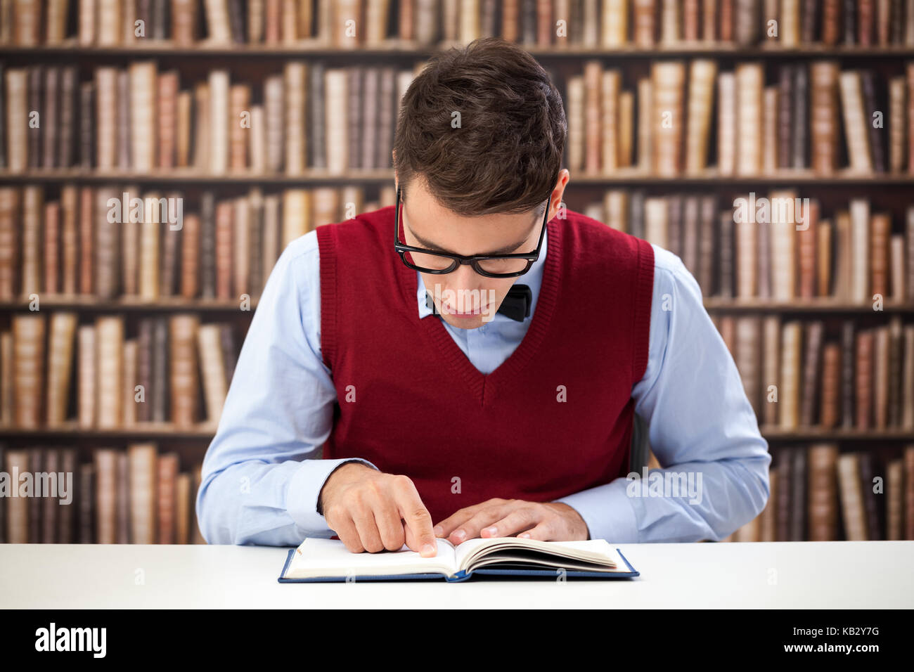 learning in library,  focused student reading book - Stock Image
