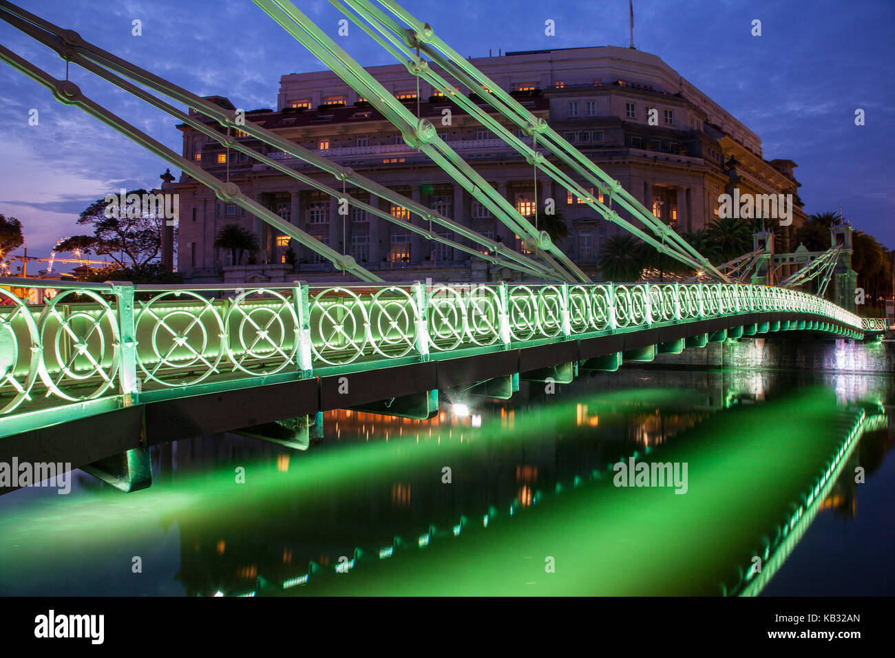Brightly lit Cavenagh Bridge is one of the oldest bridges and the only cable-stayed suspension bridge in Singapore, - Stock Image