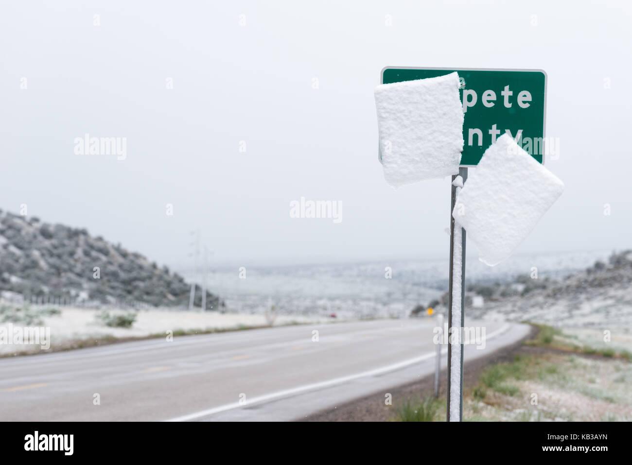 Snow slab sliding off Sanpete County sign along Highway 28 in Central Utah. - Stock Image