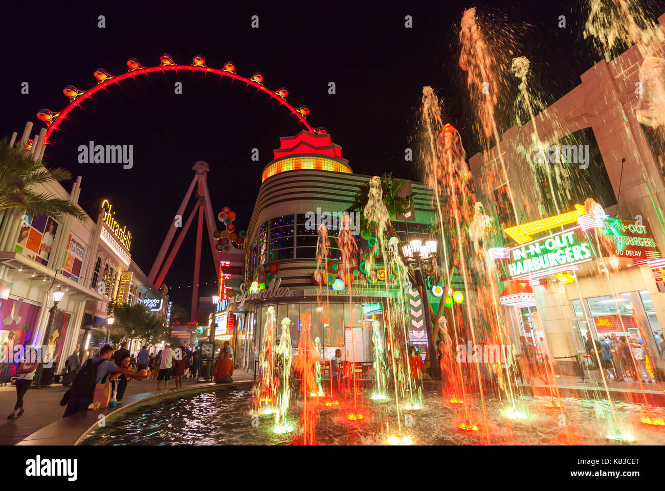 Tourists and visitors are enjoying the nighttime walking around the shoppes and stores next to The High Roller in - Stock Image