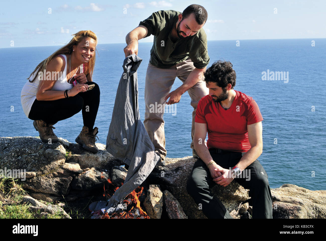 Spain, Way of St. James, pilgrim's friends while ritual combustion of the journeyling clothes in the cape Fisterra, - Stock Image